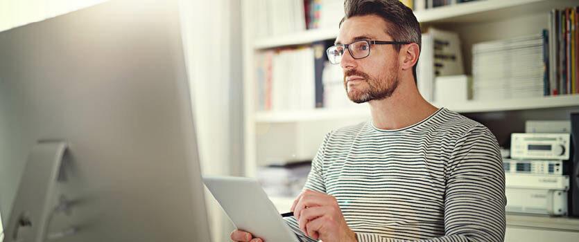 Mann mit Brille arbeitet mit Tablet und Computer