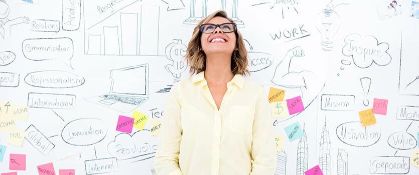 Unternehmerin steht vor einer Wand mit vielen Skizzen zum Thema Arbeit