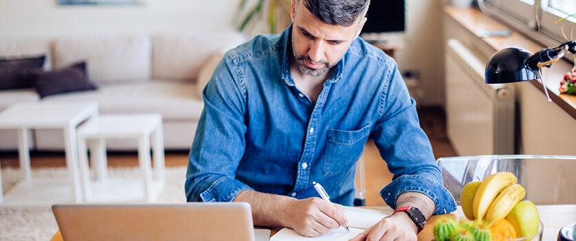 Junger Mann sitzt zuhause am Laptop und macht sich Notizen in einem Block