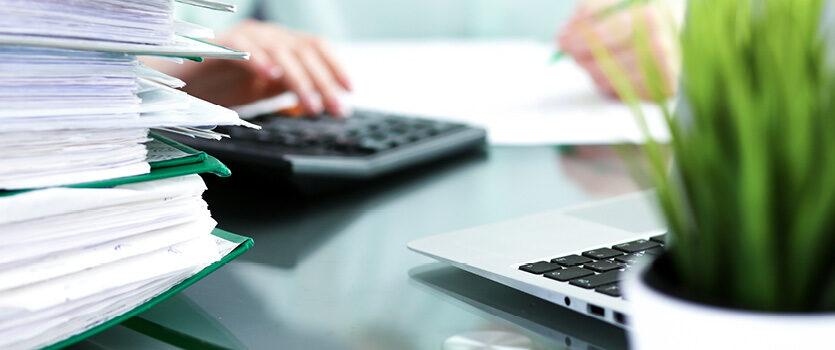 Eine Person im Hintergrund am Schreibtisch mit einem Taschenrechner und Unterlagen im Vordergund