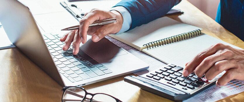 Mann am Laptop und einem Taschenrechner