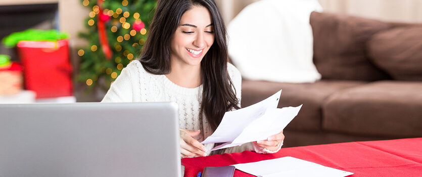 Junge Frau ist glücklich mit ihrer Gehaltsabrechnung zu Weihnachten