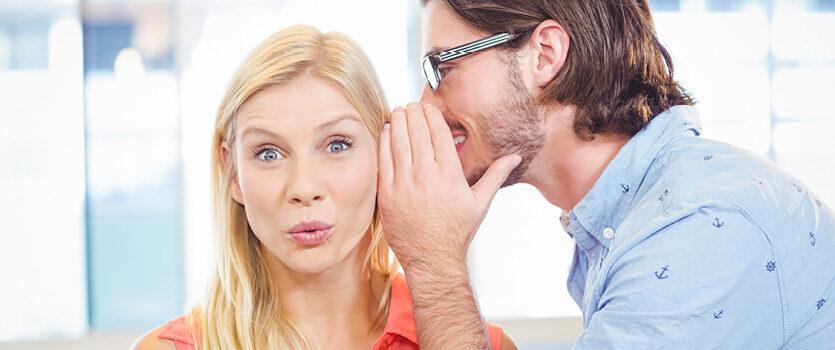 Mann flüstert Frau etwas ins Ohr, sie guckt freudig überrascht