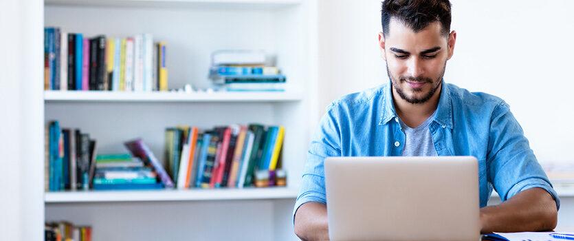 Mann im Freizeit Look vor dem Laptop