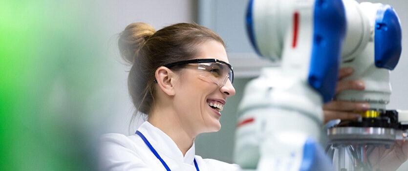 Ingenieurin lächelt bei der Arbeit am Roboter