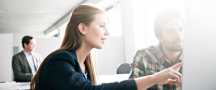 Ein Mann und eine Frau sitzen vor einem Cimputer und sie zeigt mit ihrem Finger auf den Monitor