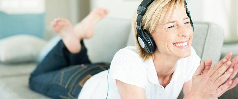 Frau liegt mit Kopfhörer auf der Couch