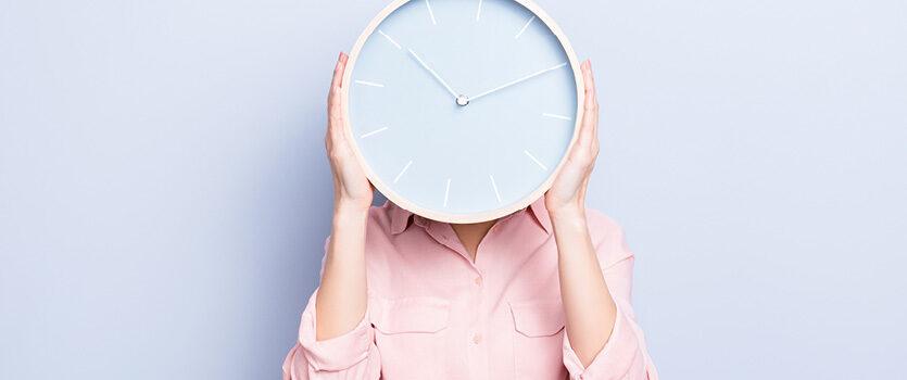 Uhr vor einem Gesicht einer Frau