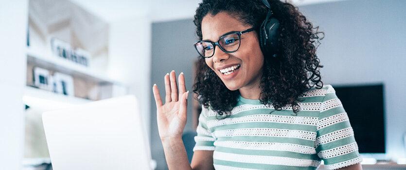 Frau mit Headset ist in einer Videokonferenz und winkt dem Gegenüber