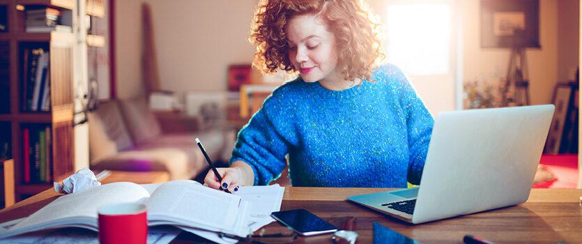 Junge Frau im Home-Office notiert sich etwas am Schreibtisch
