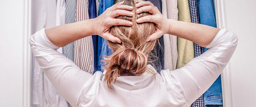 Junge Frau steht vor dem Kleiderschrank und kann sich nicht entscheiden