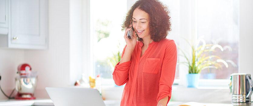 Junge Frau führt ein Telefonat in der Küche