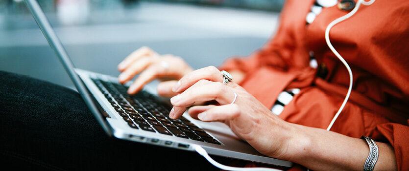 Oberkörper einer Frau mit einem Laptop auf dem Schoß