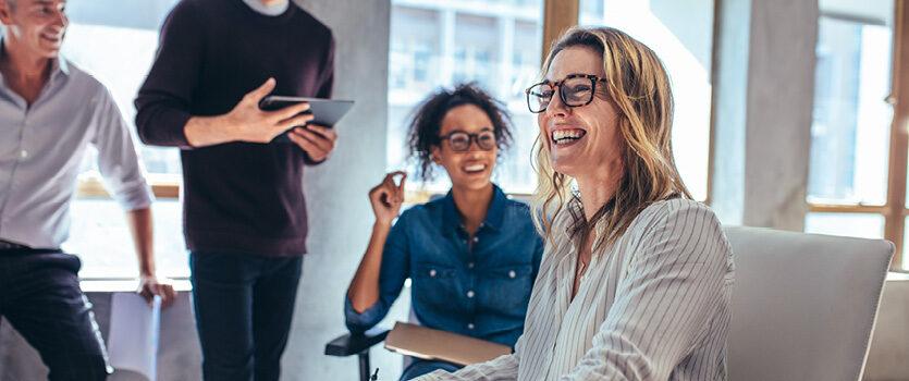 Lächelnde Frau in einem Meeting mit drei weiteren Personen
