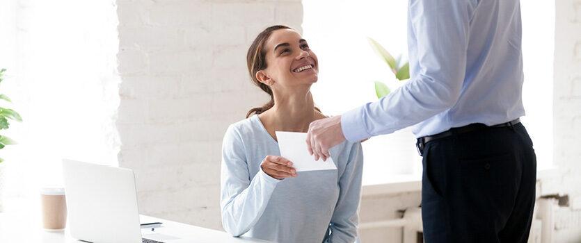 Lächelnde Frau freut sich über Dokument von einem Mann