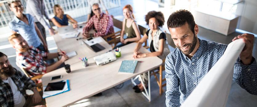 Glücklicher Unternehmer stellt dem Team seinen Businessplan vor