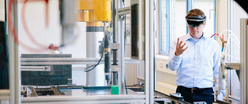 Ingenieur im Hintergrund bedient einen Roboterarm im Vordergrund mit einer VR-Brille