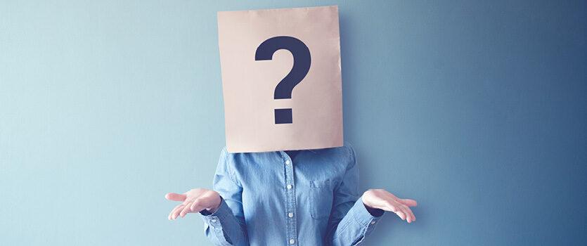Großes Fragezeichen auf einer Papiertüte, die auf dem Kopf einer Person ist