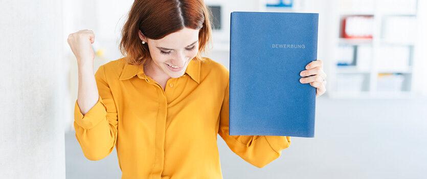 Frau mit gelber Bluse freut sich über ihre gute Bewerbung