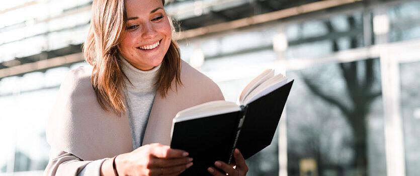 Junge Frau liest draußen ein Buch