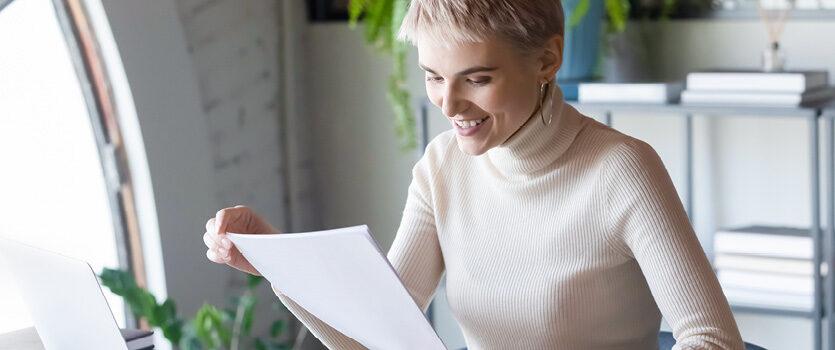 Blonde Frau schaut sich Dokumente an und ist fröhlich