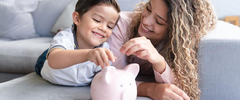 Mutter mit Sohn liegen auf dem Sofa mit einem Sparschwein