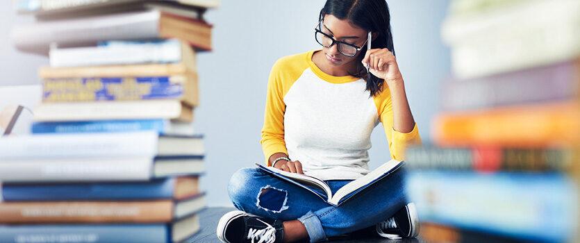 Frau mit Brille liest in einem Buch