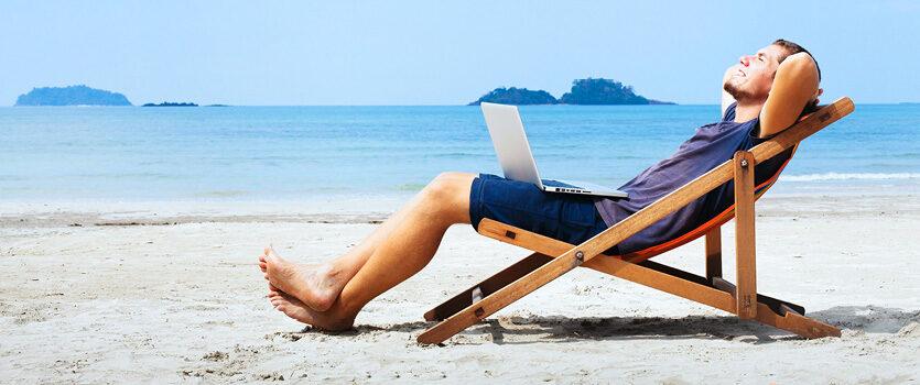 Mann mit Laptop im Liegestuhl am Strand