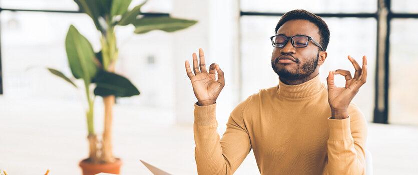 Ein Mann mit Brille meditiert und entspannt im Büro