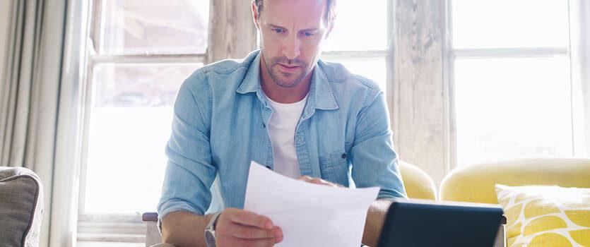 Mann liest seinen neuen Arbeitsvertrag im Wohnzimmer