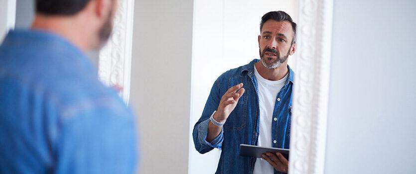 Junger Mann spricht mit dem Spiegelbild um eine Präsentation zu üben