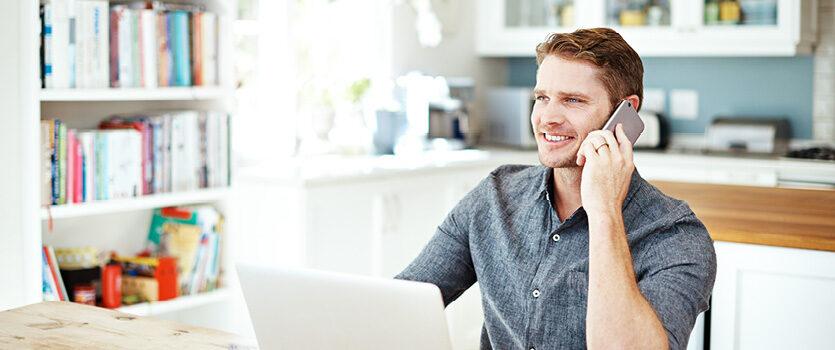 Ein Mann mit einem Mobiltelefon vor seinem PC Arbeitsplatz Zuhause