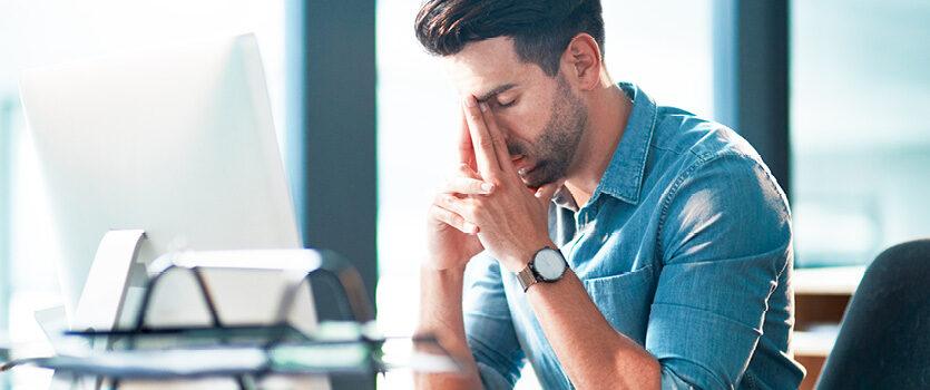 Deprimierter Mann sitzt vor einem Computer