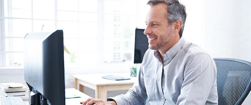 Reifer Mann arbeitet im Büro am Computer