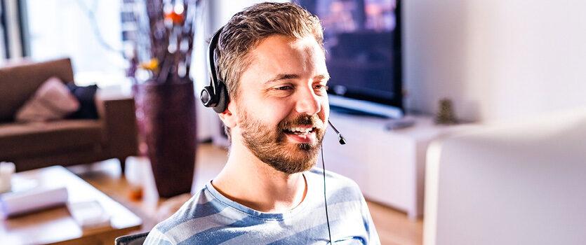 Ein Mann mit einem Headset vor seinem PC Arbeitsplatz