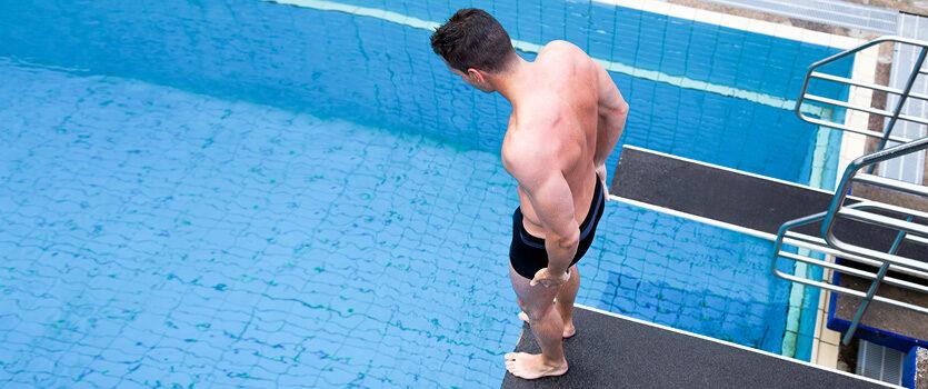 Mann im Schwimmbad auf einem Sprungturm