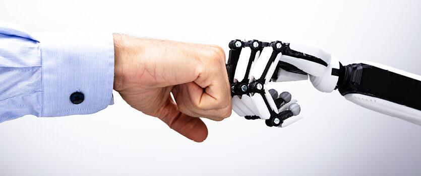 Zwei Fäuste aus einer männlichen Hand und einer Roborterhand