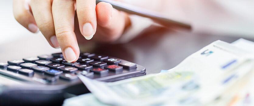 Eine Hand tippt auf einem Taschenrechner und daneben liegen Geldscheine