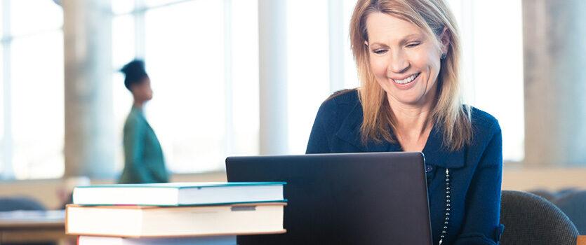Reife Frau sitzt freudig vor ihrem Laptop
