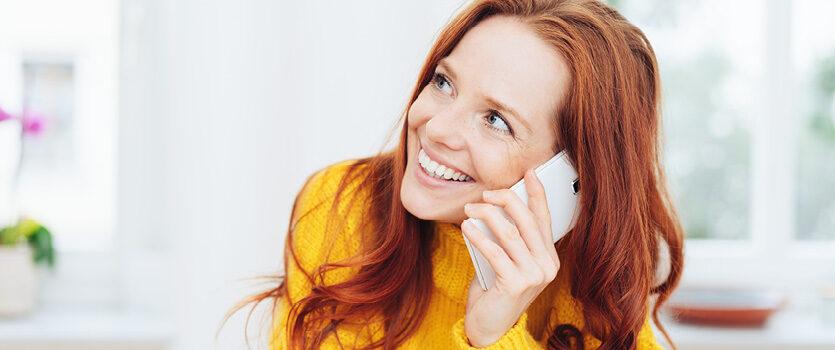 Lächelnde Frau telefoniert mit einem möglichen Arbeitgeber