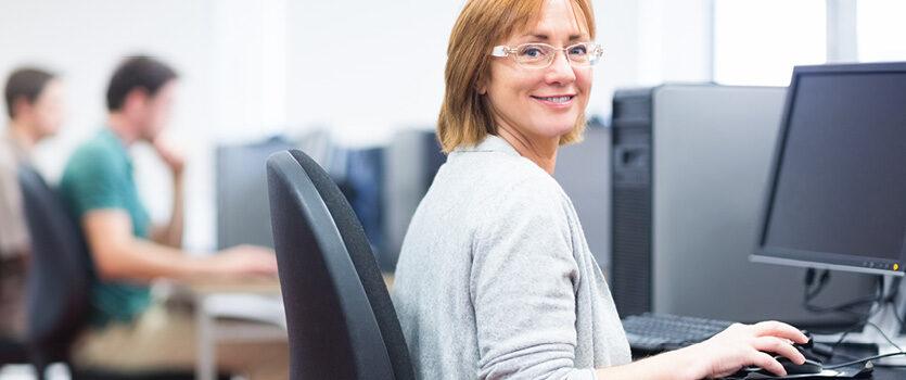 Frau sitzt mit zwei Männern in einem Schulungsraum vor einem Computer