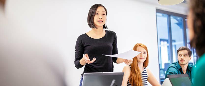 Junge sebstbewusste Frau präsentiert etwas vor ihren Kollegen