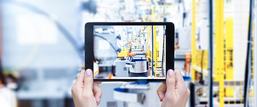 Frau hält Tablet hoch und fotografiert Maschinen