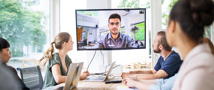 Vier Kollegen an einem Tisch in einer Videokonferenz mit einem zugeschalteten Kollegen